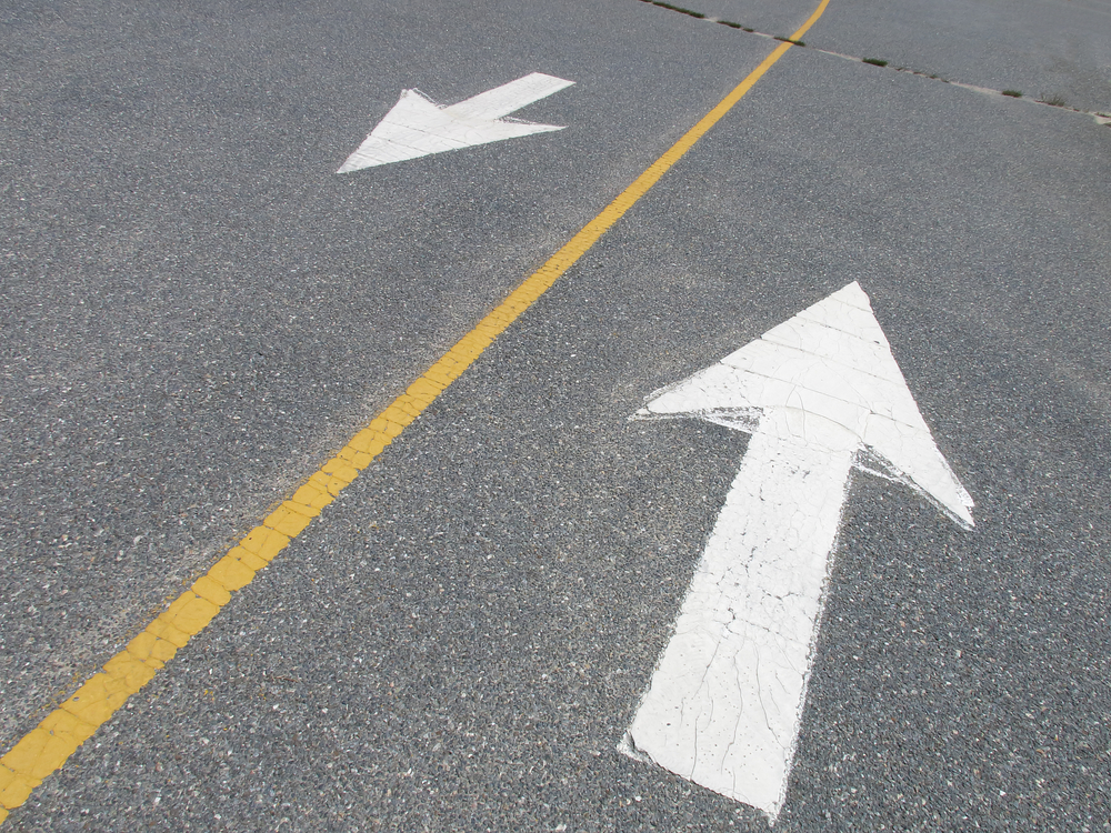 White arrows pointing in opposite directions on street